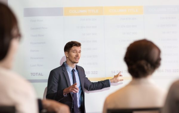 Portrait of confident successful young man standing in front of audience in conference room, making presentation, describing chart to team